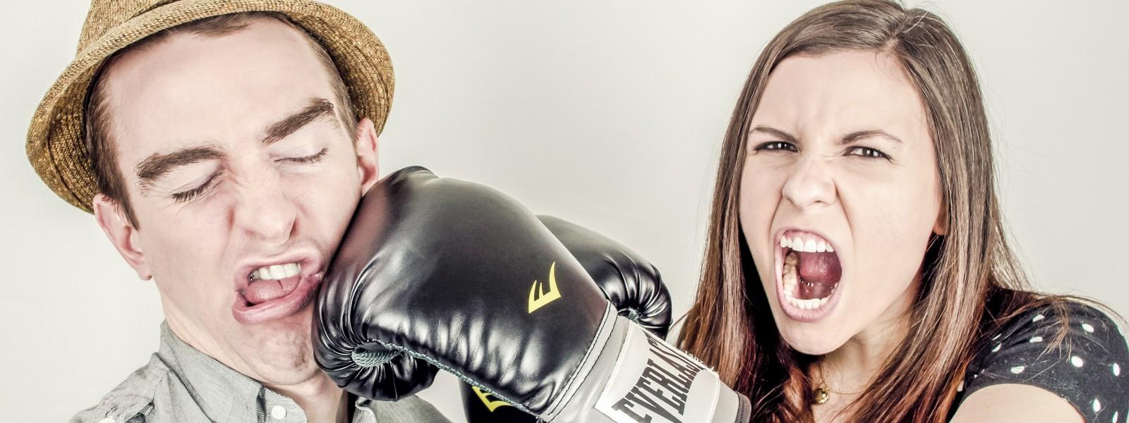woman wearing boxing gloves punching a man