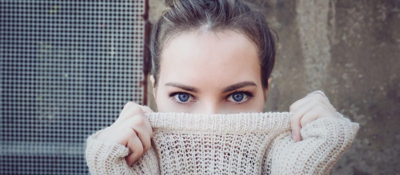 woman with blue eyes holding her sweater over her mouth and nose