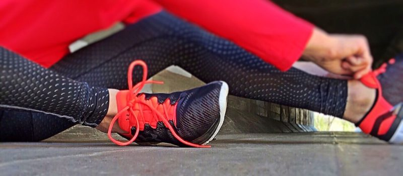 close up of a woman wearing exercise equipment siting on the ground fixing her shoes